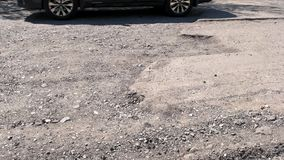 Detail view of damaged road with big potholes. Old worn road with with cracks. Bad quality road stock video footage