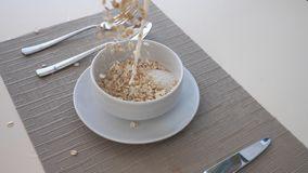 Detail view on dry crispy cereal and milk pouring into bowl. Close up of bowl with healthy breakfast and cutlery on. Table. Healthy food concept. Slow motion stock video footage