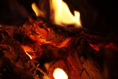 Detail view into fireplace ember wood.  Glowing embers. In hot red color Royalty Free Stock Image