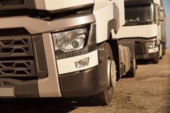 Detail view of the front part of 18 wheeled trucks in the background of the second truck. royalty free stock photo