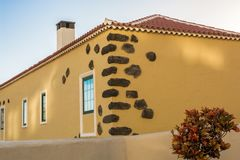 Part of a mediterranean house with yellow facade and decorative stones in the brickwork royalty free stock images