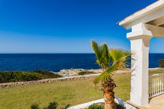 Luxury home, villa with sea view and beautiful blue sunny sky. Detail view of luxury house at coast with palm tree and view of blue sea royalty free stock photo