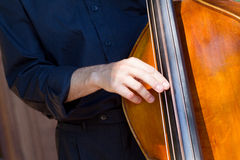 Musician playing double-bass. Detail view of a man playing double bass Stock Photo