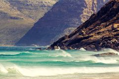 Detail view of mountains near Hout Bay, Cape Town, South Africa, seen from Noordhoek Long Beach. White sand beach and waves with spray. Noordhoek Beach is a Stock Photos