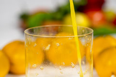 Detail view of orange's juice jet falling in a glass Royalty Free Stock Photography