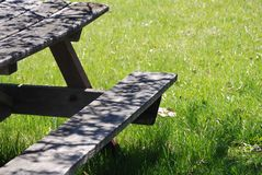Detail View Park Picnic Table. Detail view of weathered park picnic table and lawn background Royalty Free Stock Images