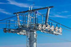 Ski lift - detail. Detail view of a ski lift pole with many rolls and steel cables with an anemometer on top Royalty Free Stock Photography