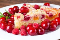 Detail view on slice of fruit pie with berries around stock photography