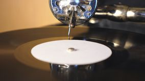 Detail view of stylus with needle sliding smoothly on black vinyl record spinning on vintage turntable. Retro concept. Blurred background. Slow motion Close up stock footage