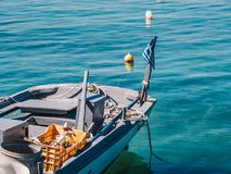 Detail view of a traditional greek fishing boat with Greek Flag in Limenas Port, Thasos Island. Thasos or Thassos is an island in the Aegean Sea, close to the stock photo