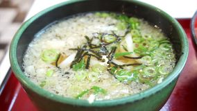 Detail view of Udon soup with tempura topping with green bowl. Detail view of Udon soup with tempura topping in green bowl stock footage