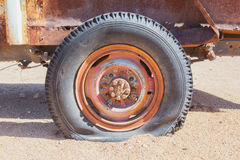 Detail of a vintage abandoned flat car tire on the side of a roa Royalty Free Stock Photos