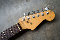 Detail of vintage electric guitar headstock. On the concrete background Royalty Free Stock Photo