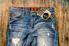 Detail of vintage jeans with classic camera Royalty Free Stock Images