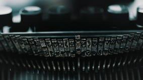 Detail of vintage typewriter metallic letters. Slow motion closeup shot of detail of vintage typewriter metallic letters stock video
