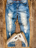 Detail of vintage weathered jeans and shoes on wood texture Royalty Free Stock Images