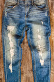 Detail of vintage weathered jeans on wood texture Stock Photos