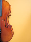 Detail of a violin against yellow background Royalty Free Stock Photos