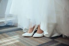 Detail von Brautbeinen mit Schuhen Hochzeitskleiderdetail stockfotos