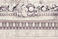 Detail von Dachgesimsen eines alten italienischen Formteilsteins mit Blumen und Franc Lizenzfreie Stockfotos