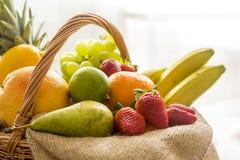 Detail von der Seite auf einem Korb voll der frischen Biofrucht auf hellem Hintergrund Stockfoto