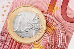 Detail von einer Euromünze auf Banknotenhintergrund Stockfotos