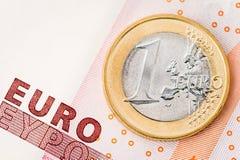 Detail von einer Euromünze auf rotem Banknotenhintergrund Lizenzfreies Stockfoto