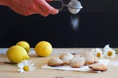 Detail von französischen süßen selbst gemachten Gebäck madeleines mit dem Zitroneneifer, der durch Hand des jungen Mannes sweetin Stockfoto