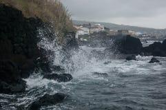 Detail von Wellen im Strand des schwarzen Sandes mit Felsen Stockbilder