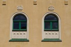 Detail von zwei Fenstern mit Verzierungen auf der Fassade Lizenzfreie Stockfotografie