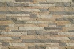 Detail of a wall of a long gray and brown brick. The facade of the building, built of natural stone. Background textur. E stock images