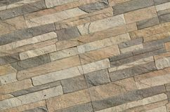 Detail of a wall of a long gray and brown brick. The facade of the building, built of natural stone. Background textur royalty free stock photography