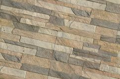 Detail of a wall of a long gray and brown brick. The facade of the building, built of natural stone. Background textur. E stock photography