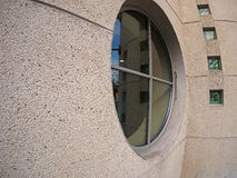 Detail of a wall of an office building with a round window Royalty Free Stock Image