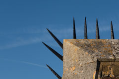 Detail of wall with row of sharp spikes along edge. Detail close-up of Tudor era brick wall with a row of sharp black spikes on top edge stock photo