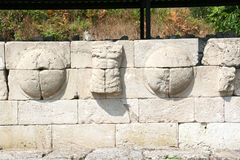 Detail of a wall of shields and torsos along the main road Dion Stock Photography