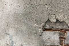 Cracked, dilapidated surface of plaster on wall. Detail of wall surface with cracked, dilapidated plaster texture. Underlying construction of stone, brick and royalty free stock photography