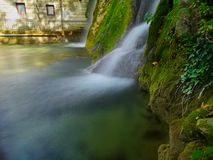 Waterfall flow, long exposure. Detail of the water flow of a small lake with stone covered with moss. Short waterfall streaming with fresh spring water royalty free stock photo