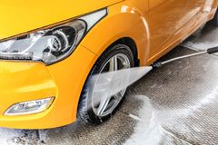 Detail on water jet spraying from the hose to yellow car front w stock image