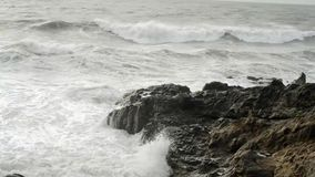 Detail of wave splashing into rocky shore stock video