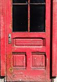 DEtail of weathered Red door with peeling paint. Detail of an old weathered and decayed exterior red door with peeling paint royalty free stock photos