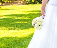Detail of wedding bouquet of flowers in hand of a bride in a garden Royalty Free Stock Image