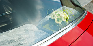Detail of a wedding car. Bouquet of flowers with white decoration in a red wedding car Stock Image
