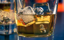 Detail of whiskey on bar table with ice Stock Images