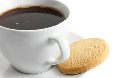 Detail of a white ceramic cup of black coffee with shortbread bi. Scuit Royalty Free Stock Photo