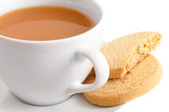 Detail of a white ceramic cup of tea with shortbread biscuits. Stock Photo
