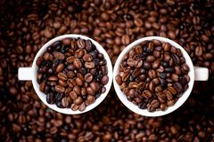 Detail of white cups of coffee filled with coffee beans Royalty Free Stock Photography