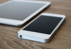 Detail of white mobile phone and white tablet. Photo of detail of white mobile phone and white tablet stock photos