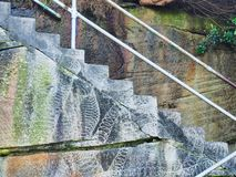 Steps on Sandstone Cliff Face, Sydney, Australia. Detail of white railed steps cut into sandstone cliff face, showing rock cutting scars and green mould moisture royalty free stock photography