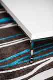 Detail of white table on striped carpet Stock Photo